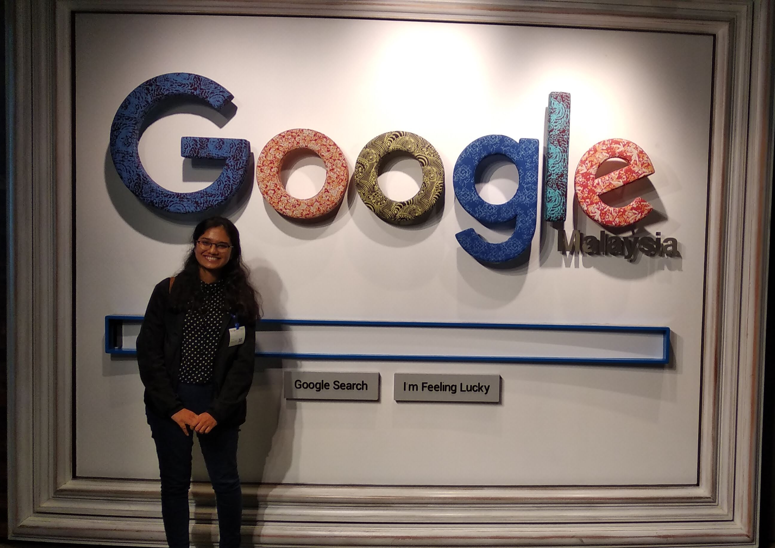 girl in front of Google Malaysia office sign board